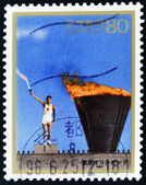 JAPAN - CIRCA 1996: A stamp printed in Japan shows the lighting of the Olympic torch Yoshinori Sakai, Tokyo 1964, circa 1996 — Stock Photo