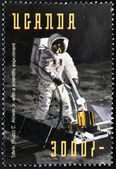 UGANDA - CIRCA 1998: Stamp printed in Uganda shows Edwin Buzz Aldrin conducts Soil Samples experiments for life forms Earth from the moon during the Apollo11 Space Mission to the Moon, circa 1998 — Foto Stock