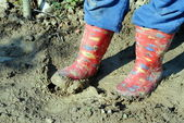 Red kid boots, dirty in the mud — Foto de Stock