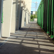 Stock Photo: Shady path with wall and green pipes