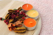Three candles with dried flowers in wooden dish — Stock Photo