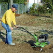 Middle age man with a rototiller in the garden — 图库照片