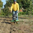 Middle age man with a rototiller in the garden — Stock Photo #9057390
