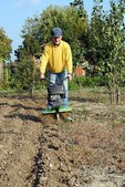 Middle age man with a rototiller in the garden — Stock Photo