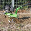 Green rotary tiller working in garden — Stok Fotoğraf #9134050