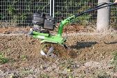 Gröna rotary tiller arbetar i trädgården — Stockfoto