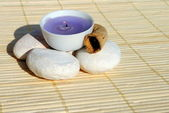 Lighted purple candle on bamboo place mat — Stock Photo