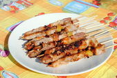 Cocked pork kabobs grilled on skewers in a plate — Stock Photo
