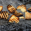 Slices of grilled bread rubbed with garlic on a barbecue — Stock Photo