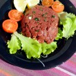 Raw ground beef with vegetables on a black dish — Stock Photo