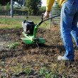 Middle age man with a rototiller in the garden — Stok fotoğraf
