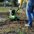 Middle age man with a rototiller in the garden — Stockfoto
