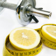 Stock Photo: Grapefruit and dumbell on white