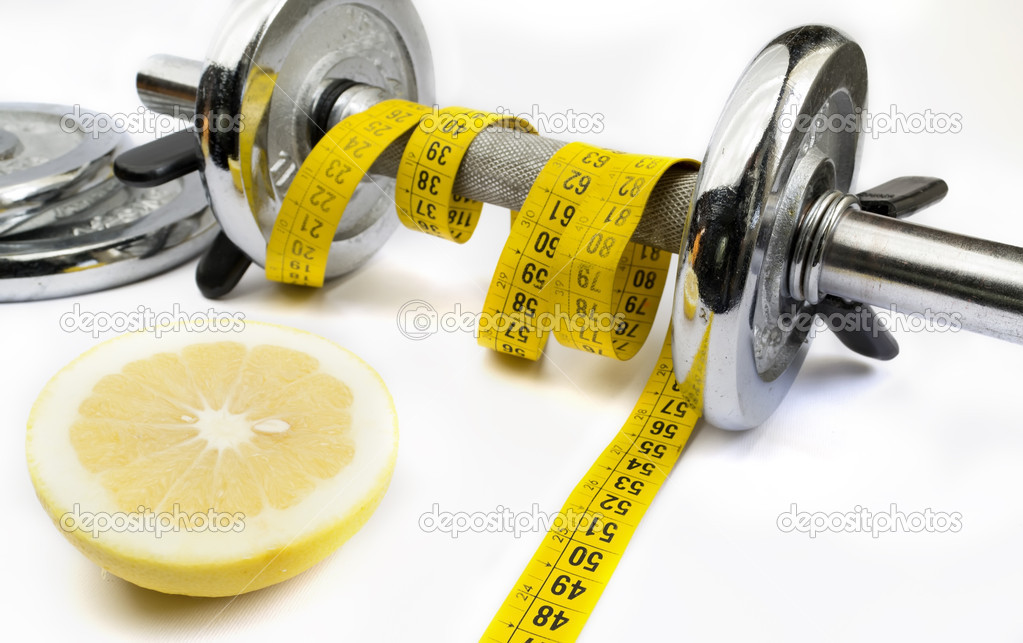 Half grapefruit and meter tape wrapping a metal dumbell  Stock Photo #8013962