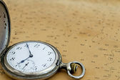 Old fob watch on a map — Stock Photo
