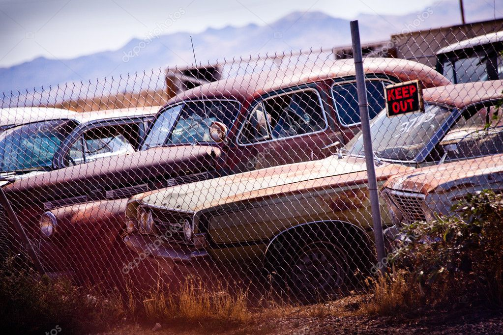 "A junkyard with old, wrecked cars and a signal ""keep out"". Vignetting and strong contrast have been added to make the shot more dramatic. — Stock Photo #10620765"