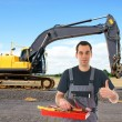 Construction worker in front of a excavators — Stockfoto