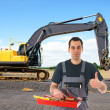 Construction worker in front of a excavators — Stock Photo