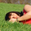 Stock Photo: Dreaming pretty girl in green grass
