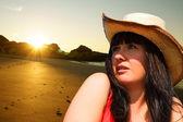 Hezká dívka na pláži, pozorování východu slunce — Stock fotografie