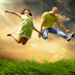 Fun couple in jump on the outdoor background — Stock Photo #8782428