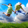 Fun couple in jump on the outdoor background — Lizenzfreies Foto