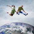 Fun couple in jump over the Planet Earth — Stock Photo #8782530