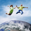 Royalty-Free Stock Photo: Fun couple in jump over the Planet Earth