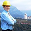 Young architect wearing a protective helmet standing on the moun — Stock Photo #8782753