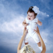 Child in white in mother hands under sky background — Stock Photo