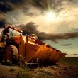 Yellow tractor on sky background — Stock fotografie