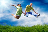 Fun couple in jump on the outdoor background — Stock Photo