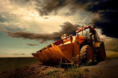 Yellow tractor on sky background — Stok fotoğraf