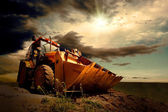 Yellow tractor on sky background — Stockfoto
