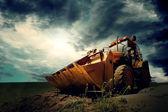 Gökyüzü arka plan üzerinde sarı traktör — Stok fotoğraf