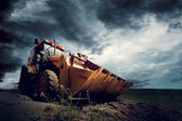 Yellow tractor on sky background — Stock Photo