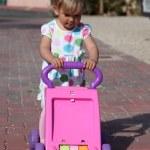 Toddler girl pushing toy trolley — Stock Photo #10584602