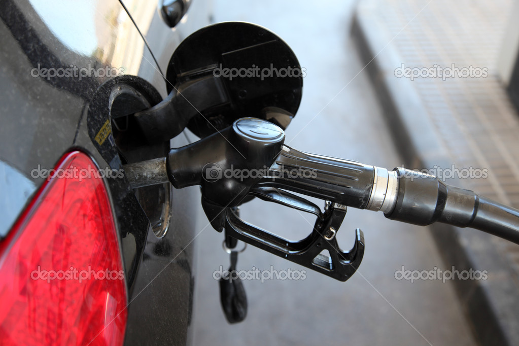 Gas station pump nozzle in the cars fuel tank — Stock Photo #10584594