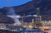 Oil refinery facilities illuminated at night — Stock Photo