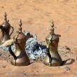 Traditional Arabic coffee pots at fireplace in the desert - Foto Stock