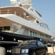 Bentley convertible parked in front of a luxury yacht in Saint Tropez, France - Foto de Stock