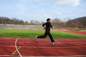 Niña corriendo en un estadio — Foto de Stock