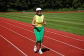 Aktivní senior žena běhat na stadionu — Stock fotografie