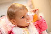 Baby girl drinking out of a cup — Stock Photo