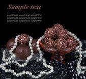 Pralinen-sortiment auf platte, mit weißen und schwarzen perlen — Stockfoto