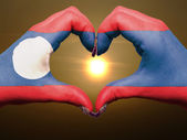 Heart and love gesture by hands colored in laos flag during beau — Stock Photo