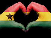 Heart and love gesture by hands colored in ghana flag for touris — Stock Photo