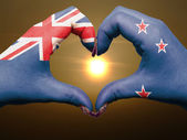 Heart and love gesture by hands colored in new zealand flag duri — Stock Photo