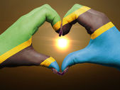 Heart and love gesture by hands colored in tanzania flag during — Stock Photo