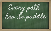 Expression - Every path has its puddle - written on a school bl — Stock Photo